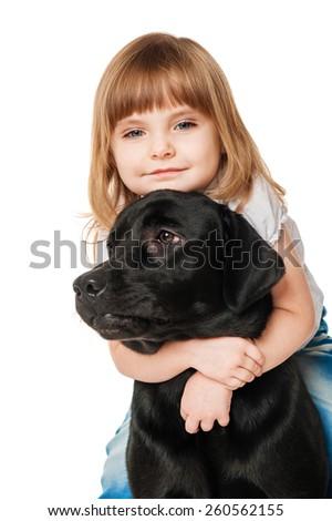 Beautiful girl hugging a black Labrador - stock photo