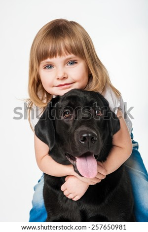 Beautiful girl hugging a black Labrador, on a gray background - stock photo