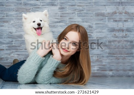 Beautiful girl huging Samoyed dog - stock photo
