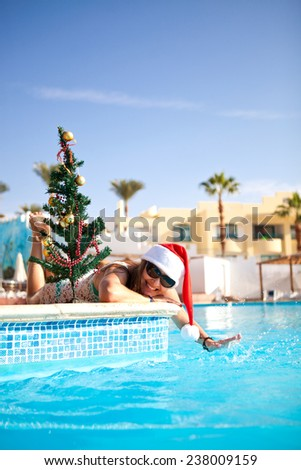 Beautiful girl in a bathing suit and a red Christmas hat lies near the pool with a Christmas tree summer day - stock photo