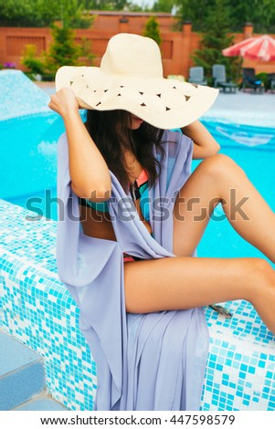 beautiful girl in a bathing suit and tunic pool