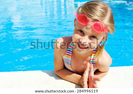 beautiful girl in a bathing suit, swim cap, goggles, holding on overboard in a swimming pool - stock photo