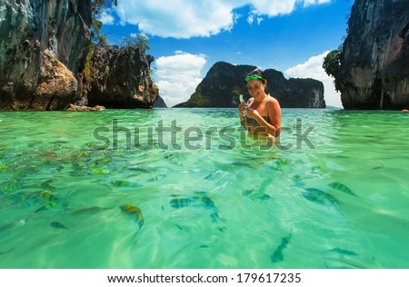 beautiful girl in a bathing suit with a mask and snorkel standing in the water of a flock of colorful fish . Bay at Phi phi Island, karst mountains, Tropical beach , Andaman Sea, Krabi, Thailand - stock photo
