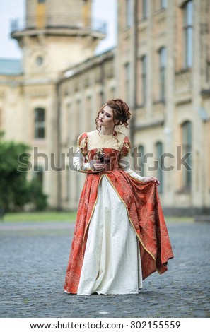 Beautiful girl in a beautiful old dress like a princess or a fairy castle in the background - stock photo