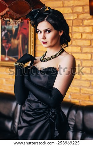 Beautiful girl in a black dress and gloves posing . Party in style gangsters forties. - stock photo