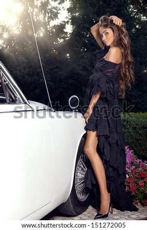 Beautiful girl in a black dress standing near the vintage car