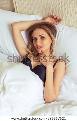 Beautiful girl in a black underwear is looking at camera and smiling while lying in bed in her room