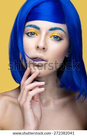 Beautiful girl in a bright blue wig in the style of cosplay and creative makeup. Beauty face. Art image. Picture taken in the studio on a yellow background. - stock photo