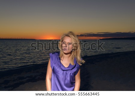 Beautiful girl in a bright violet dress by the sea.