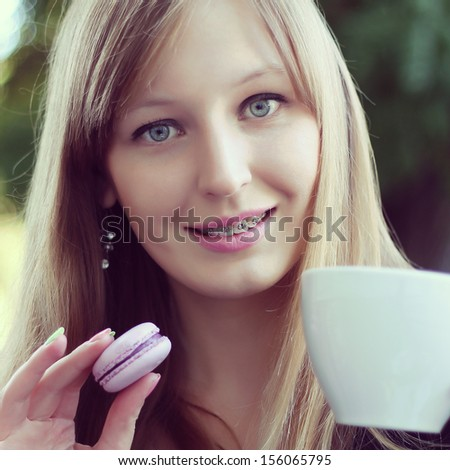 Beautiful girl in a cafe eating sweet traditional French Cake - stock photo