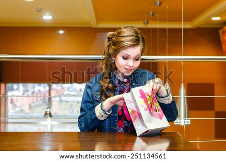 Beautiful girl in a cafe looking in gift bag - stock photo