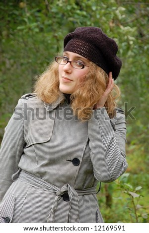 Beautiful girl in a coat over a green background - stock photo