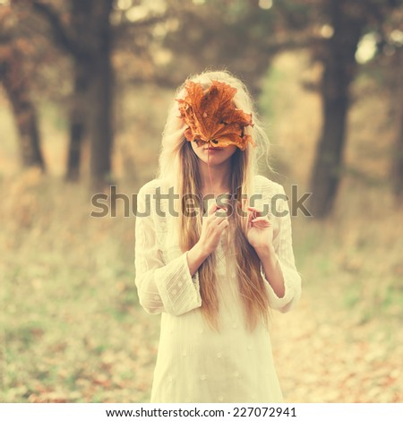 beautiful girl in a dress in the autumn in a mask of dry leaf - stock photo
