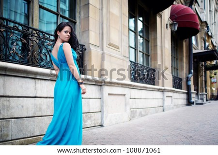 Beautiful girl in a dress on the street - stock photo