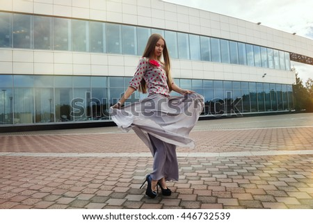 Beautiful girl in a dress stands near a glass building and spinning