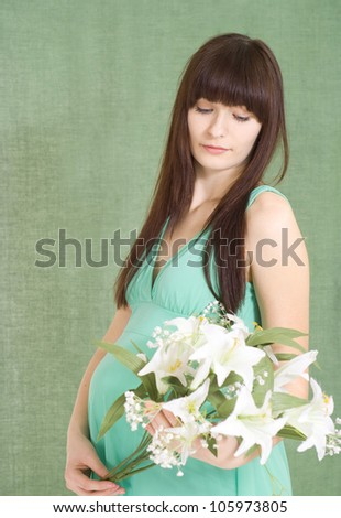 Beautiful girl in a dress with a neckline is expecting a baby - stock photo