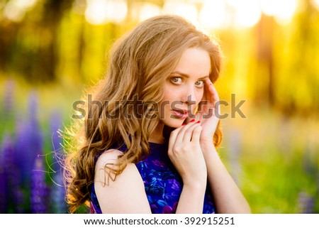 beautiful girl in a field of purple wildflowers at sunset on a Sunny day - stock photo