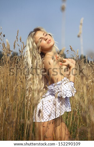 beautiful girl in a field with flowers at sunset - stock photo