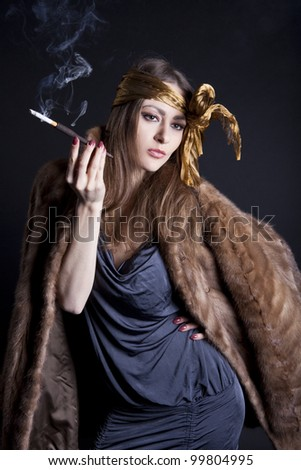 beautiful girl in a fur coat with a mouthpiece - stock photo