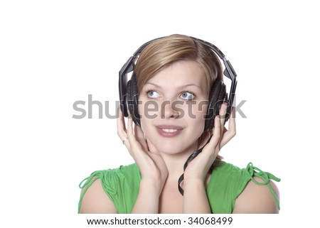 beautiful girl in a green dress listening to music with big headphones, isolated on white