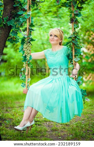 beautiful girl in a green dress on a swing in the summer garden.