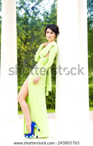 Beautiful girl in a green dress on walk - stock photo