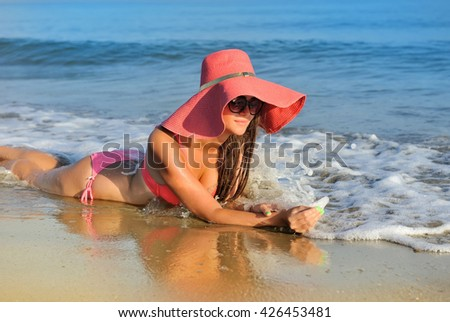 Beautiful girl in a hat on a background of the sea - stock photo