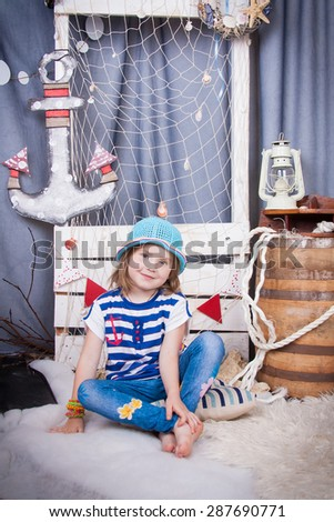Beautiful girl in a hat sitting barefoot near the barrel, marine networking and cables. Cute little girl smiling on the background of summer sea scenery. Happy and carefree childhood - stock photo