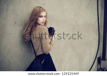 beautiful girl in a hipster style with a camera against the wall - stock photo