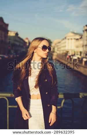 beautiful girl in a lavender cloak and sunglasses posing on the street on the bridge
