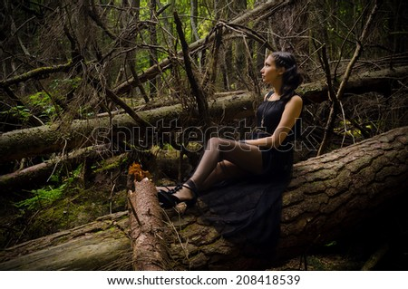 beautiful girl in a long black dress in a mystical forest - stock photo
