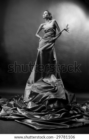 Beautiful girl in a long dress holds exotic flower in a hand. - stock photo