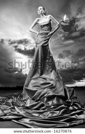 Beautiful girl in a long dress holds exotic flower in a hand. Against backdrop of cloudy skies - stock photo