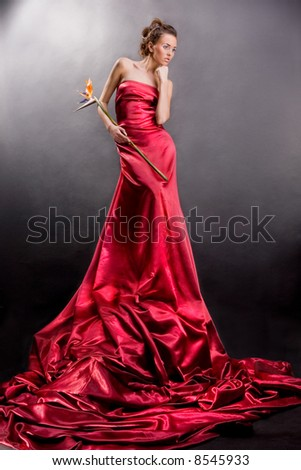 beautiful girl in a long red dress holds an exotic flower in a hand - stock photo