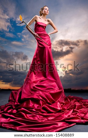 Beautiful girl in a long red dress holds an exotic flower in a hand. Against backdrop of cloudy skies - stock photo