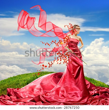 Beautiful girl in a long red dress holds exotic flower in a hand - stock photo