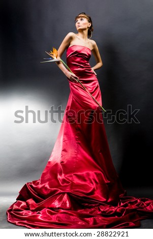 Beautiful girl in a long red dress holds exotic flower in a hand.
