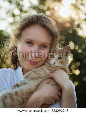Beautiful girl in a park holding a kitten in her arms. - stock photo