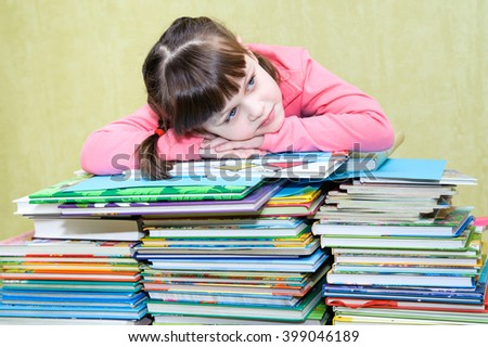 Beautiful girl in a pink jacket leaned against a stack of books - stock photo