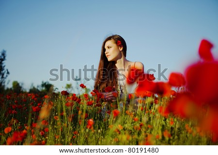 beautiful girl in a poppy field at sunset - stock photo