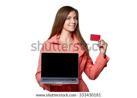 Beautiful girl in a raincoat  hold laptop computer and credit card on a white background. - stock photo