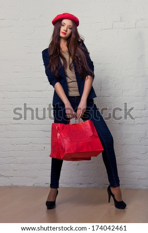 Beautiful girl in a red beret holding bags. French Style - stock photo