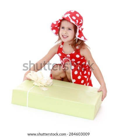 Beautiful girl in a red dress and hat polka dot bent down to examine a large box with a gift- isolated on white background - stock photo