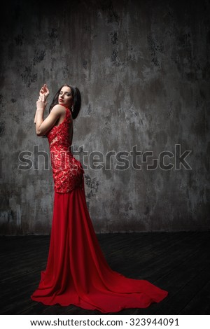 Beautiful girl in a red dress in studio