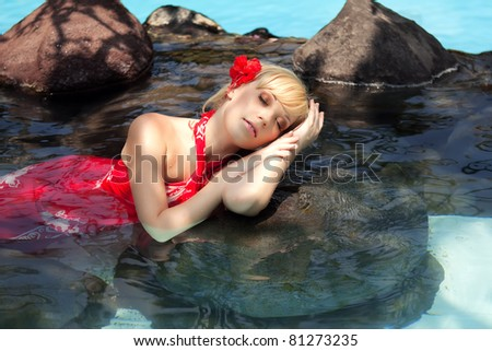 beautiful girl in a red dress lying in the water - stock photo