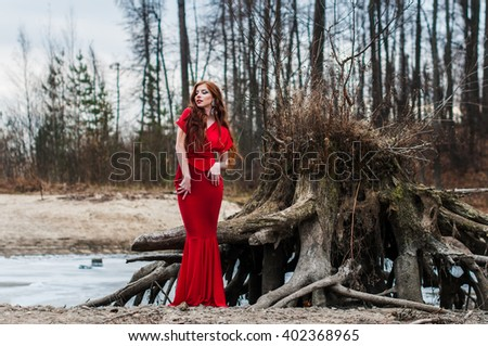 Beautiful girl in a red dress on a sandy beach