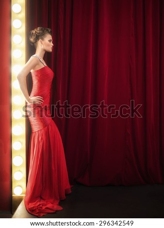Beautiful girl in a red dress on the scene - stock photo