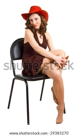 beautiful girl in a red hat and brown dress sits on a chair. Isolation on a white background. - stock photo