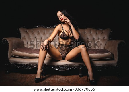 Beautiful girl in a sexy lingerie  on a sofa - stock photo