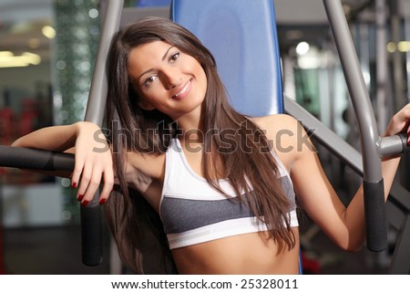Beautiful girl in a sports hall does a break during training